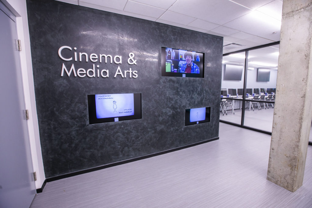 """The wall of screens outside the Buttrick elevator in the basment with a sign saying """"Cinema & Media Arts"""" and three TV screens showing student films"""