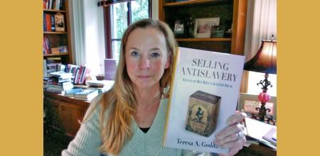 Professor Nelson holding up Teresa Goddu's book Selling Antislavery